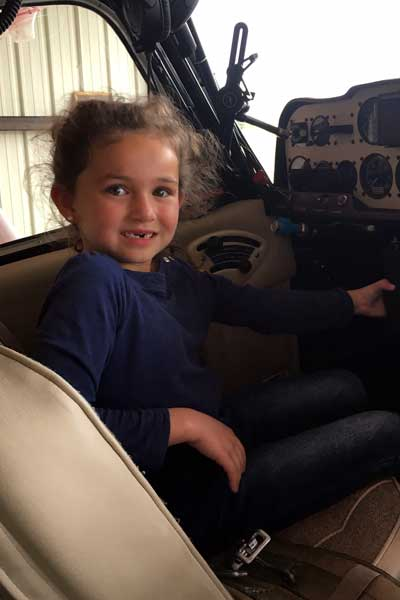 Olive, age 5½, seated at the controls of my plane